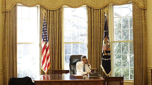 President Barack Obama makes a call from the Oval Office on his first full day on the job.