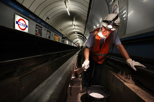 A worker cleans the ceramic insulator pots under the live rail at Pimlico. The London Tube was the first underground railway to operate electric trains.
