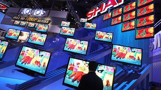A man passes the Sharp HD television display at the 2008 Consumer Electronics Show in Las Vegas, Nevada.