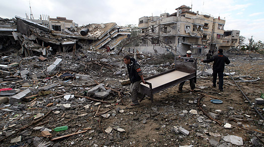 Palestinian carrying a bed walk past the rubble of a building destroyed overnight following an Israeli air strike in Rafah in the southern Gaza Strip on January 8, 2009.