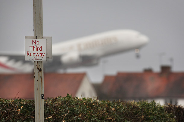 A airliner takes off from Heathrow airport as seen from the village of Sipson
