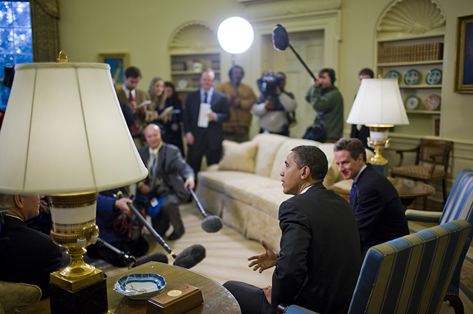 Surrounded by media, U.S. President Barack Obama meets with Treasury Secretary Timothy Geithner in the Oval Office at the White House in Washington.
