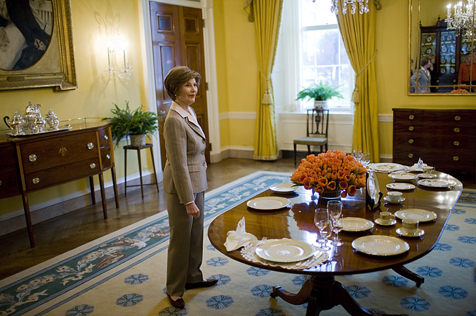 First lady Laura Bush gestures while showing off some of the new White House China in the Old Family Dining Room of the White House in Washington.