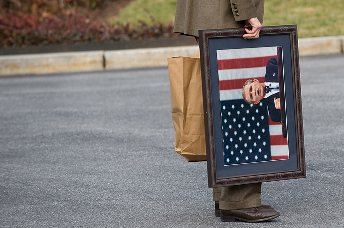 A White House staffer carries a framed photograph of US President George W. Bush outside the West Wing of the White House