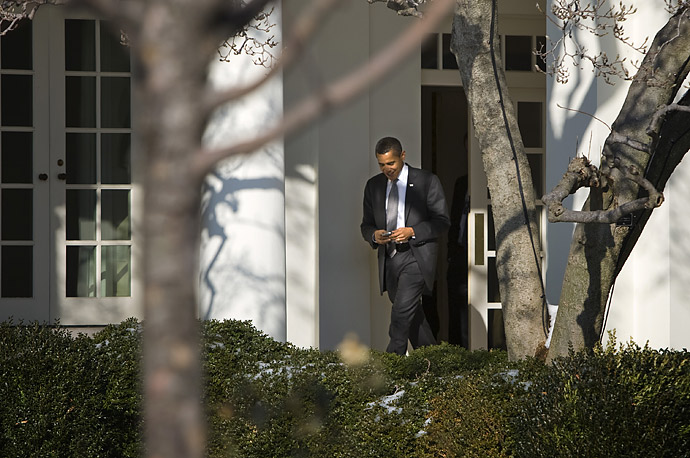President Barack Obama uses his new secure PDA as he makes his way toward the Oval Office.