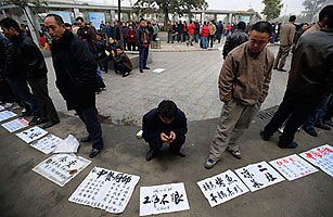 Migrant workers wait for employers on a street in Chengdu, Sichuan province, on February 2, when Beijing announced about 20 million migrant workers have lost their jobs because of the economic downturn