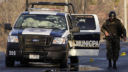A Mexican soldier walks near a bullet-riddled police vehicle at the scene where three police officers were killed in Ciudad Juarez, northern Mexico, Tuesday, Feb. 17, 2009.