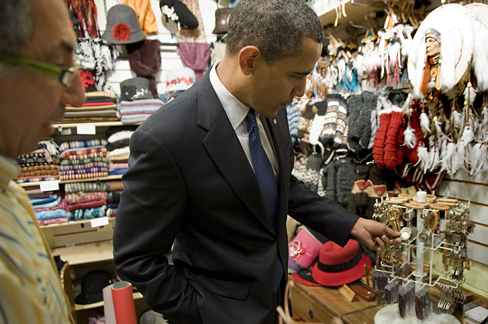 US President Barack Obama (C) shops at OXXO Silk & Gift for a keychain while visiting the Byward Market Square in Ottawa, Canada