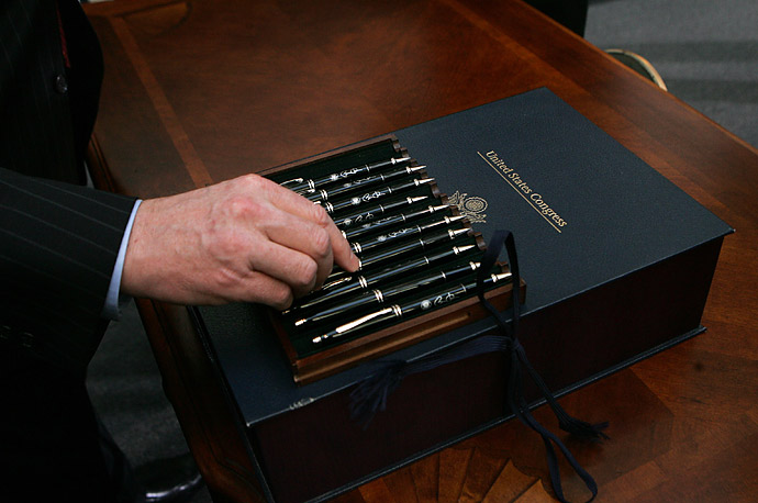 A White House staff member arranges the pens President Obama used to sign the $787 billion economic stimulus bill  at the Denver Museum of Nature and Science.