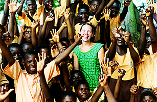 A Cross Cultural Solutions volunteer poses with school children in Ghana.