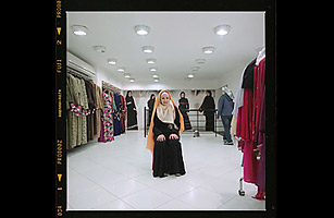At a store in Cairo, an assistant places a white scarf of nontransparent material directly on the head of another assistant, ensuring that all of the hair is concealed.