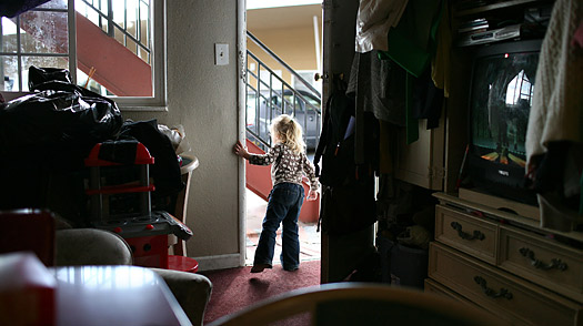 A child looks out the door of her motel room in West Sacramento, California. The girl's family was evicted from the house they were renting after her father lost his job. The couple