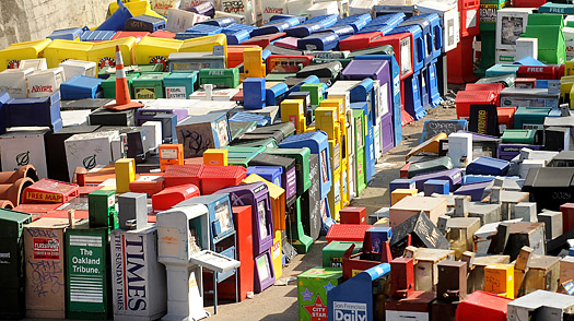 Disused newspaper racks clutter a storage yard without newspapers