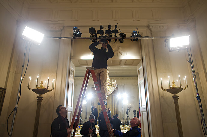 Media press photographers mount cameras above the entrance to the East Room, where President Barack Obama held a news conference at the White House in Washington, DC.