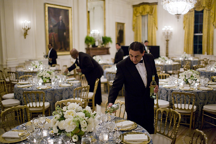 White House butlers pour wine in the candle-lit East Room before U.S. President Barack Obama plays host to congressional committee chairmen for a dinner.