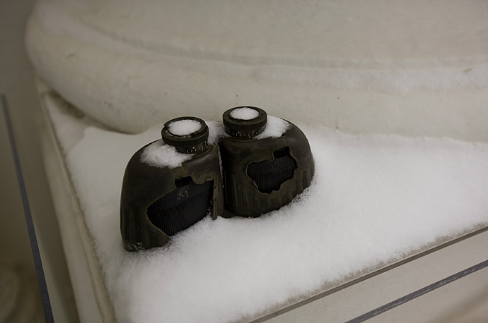 Secret Service binoculars sit on a ledge covered in snow, next to the front entrance of the White House in Washington.
