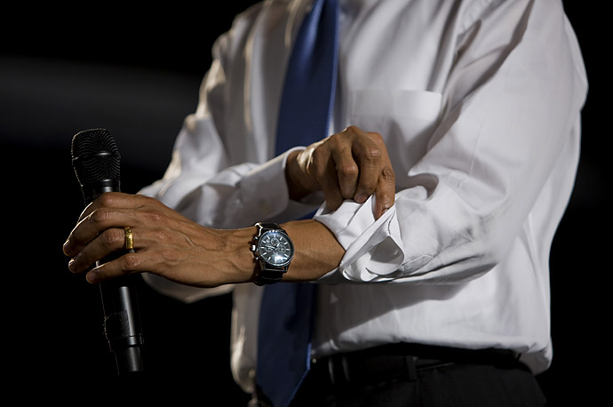 President Barack Obama adjusts his sleeves at a town hall meeting at the Orange County Fair and Event Center in Costa Mesa, California.