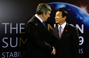 Britain's Prime Minister Gordon Brown greets his Japanese counterpart Taro Aso upon his arrival at the G20 summit in London on April 2, 2009