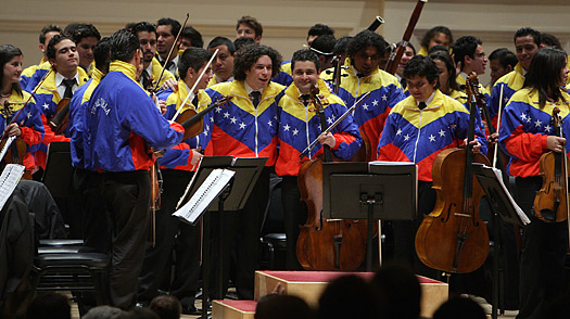 Venezuelan conductor Gustavo Dudamel (C) receives a standing ovation after leading his Simon Bolivar Youth Symphony Orchestra during his first appearance at Canergie Hall in New York, 11 November 2007.