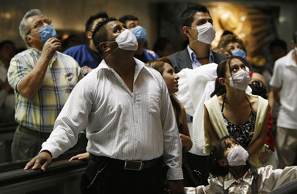 People wearing protective masks pay respects to Our Lady of Guadalupe
