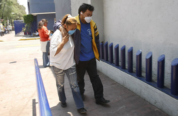 Erika Cruz, left, helps her husband Miguel Anguel Esquivel walk toward the emergency entrance of the National Institute of Respiratory Illnesses in Mexico City