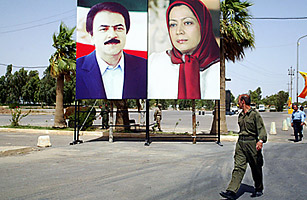 An Iranian militant of the opposition People's Mujahedin (MEK) passes pictures of leaders Maryam Rajavi (L), president of the National Council of Resistance of Iran, the political