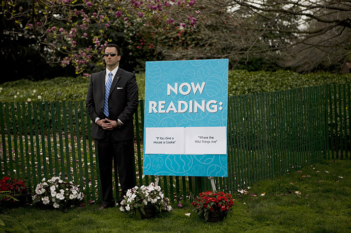 A Secrect Service agent stands guard as President Obama reads a book to a group of children during the annual White House Easter Egg Roll on the South Lawn.