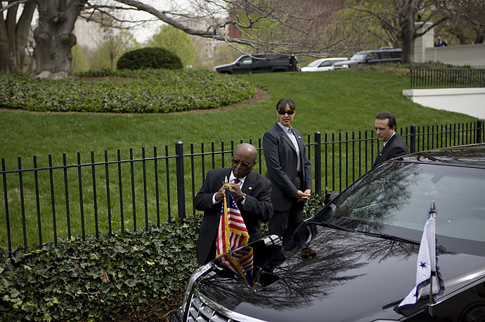 A White House staff member attaches a flag to the Presidential limousine.