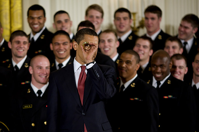 President Obama looks thru a replica championship ring while he presented the Commnader in Chief trophy to the United States Naval Academy Football team at the White House.