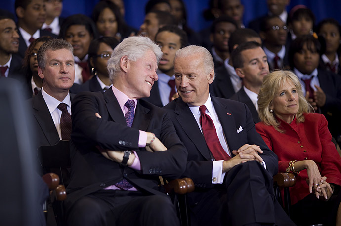 Former President Bill Clinton and Vice President Joe Biden watch the signing ceremony for the Edward M. Kennedy Serve America Act at the SEED School of Washington.