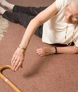 an elderly lady lying on the floor reaching out for her walking stick