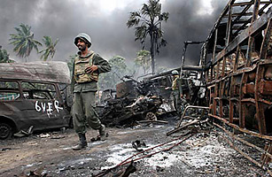Sri Lankan troops walk amongst debris inside a combat zone on May 17, 2009, while evacuating Tamil civilians from the area.