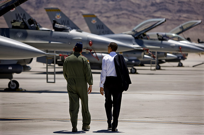 U.S. President Barack Obama walks past F-16 aircraft with Brigadier General Stanley Ted Kresge at Nellis Air Force Base in Las Vegas, Nevada.