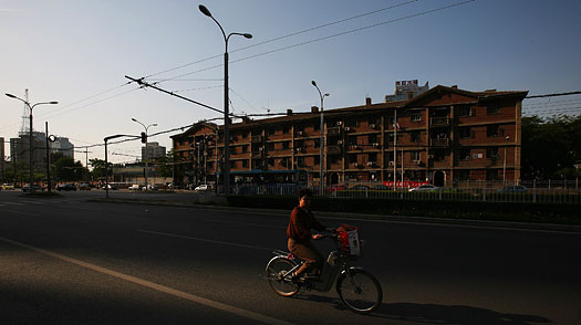 A woman rides her electric bicycle past a residential block in Beijing, China