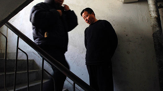 Lawyer Gao Zhisheng steps aside to let a woman pass on the stairway of his safehouse in northern China on Dec. 7, 2005