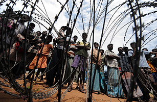 Internally displaced Sri Lankan people wait behind barbed wire during a visit by United Nations Secretary-General Ban Ki-moon at Menik Farm refugee camp in Cheddikulam on May 23, 2009