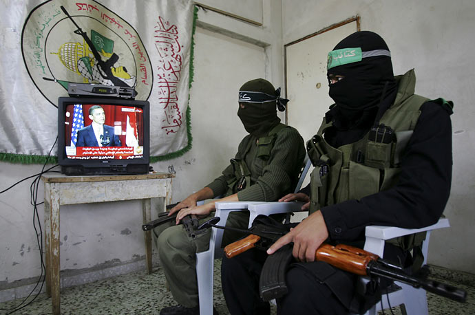Members of Hamas, wearing masks to conceal their identity, watch President Obama's speech at their training base in the Gaza Strip.