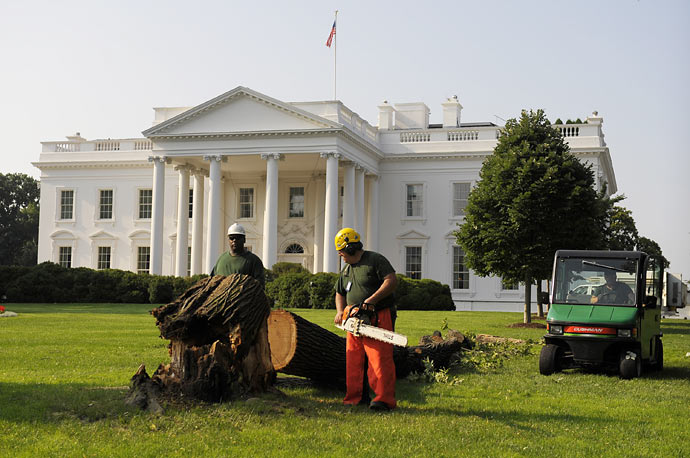 Members of the U.S. Park Service remove the remaining debris from a tree that fell during an overnight storm on the North Lawn of the White House
