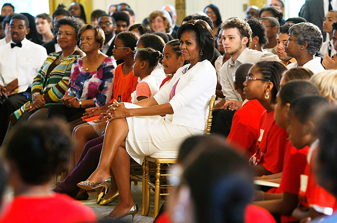 U.S. First Lady Michelle Obama (C) watches a concert with daughters Malia and Sasha at the East Room of the White House June 15, 2009 in Washington, DC.