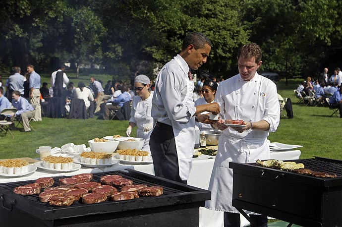 President Obama grills with Chef Bobby Flay as he hosts an outdoor barbeque for young men from local schools on the South Lawn of the White House.