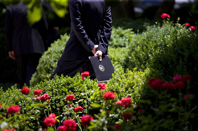 A White House staff member holds a leather folio in the Rose Garden