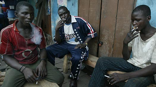 Three men smoking on a street in Lagos