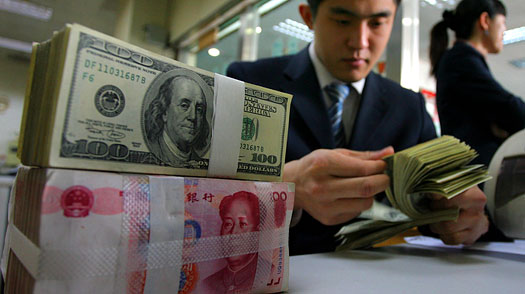 A Chinese bank employee counts U.S. dollars in Shandong province