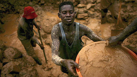 Men sift through buckets of dirt while looking for gold at an abandoned industrial mine in Mongbwalu, Congo.