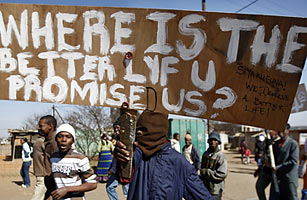 A protester holds a placard during a peaceful protest march in the Ramaphosa squatter settlement, east of Johannesburg