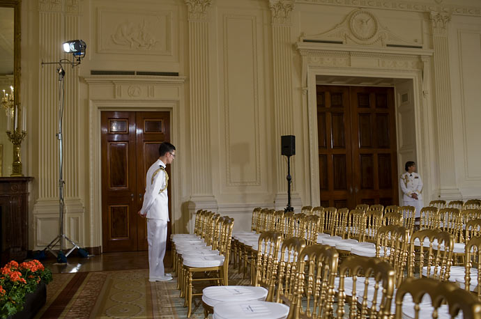 Ushers wait for the arrival of guests before President Barack Obama speaks in the East Room of the White House.