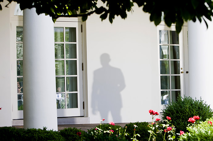 A shadow of President Barack Obama falls on the White House as he departs the Rose Garden.