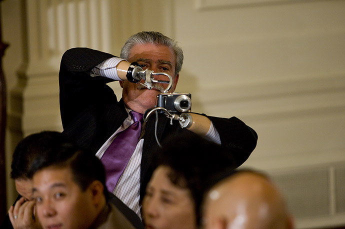 A member of the audience takes a photograph during an anniversary event for the Americans with Disabilities Act with in the East Room at the White House.