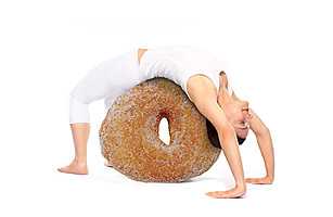 Woman stretching over doughnut.