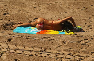 A woman sunbathes on the beach during the 62nd International Cannes Film Festival in May 2009